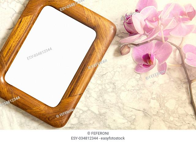 Image of a flat lay mockup concept with orchids and wooden frame
