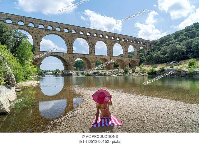 Woman wearing pink hat sunbathing by Pont du Gard in Vers-Pont-du-Gard, France