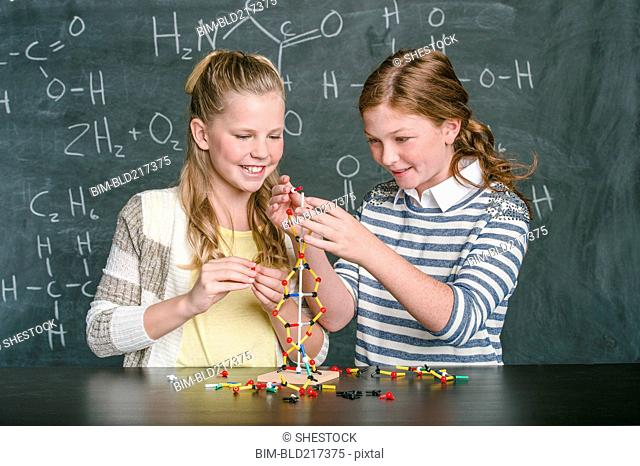 Caucasian students examining molecular model in science class