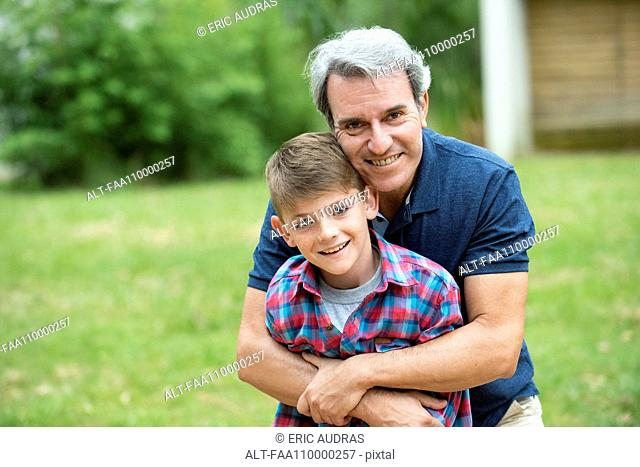 Grandfather embracing grandson outdoors, portrait