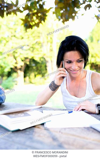 Smiling woman sitting in a park telephoning with smartphone