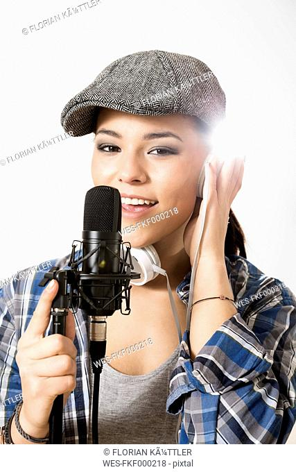 Portrait of young woman singing in microphone, smiling