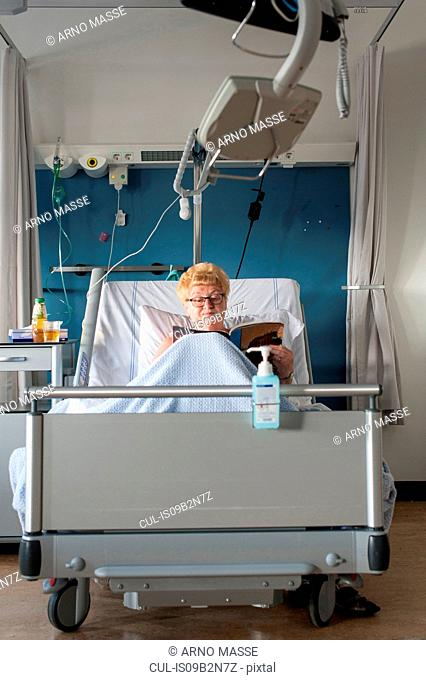 Patient in hospital bed reading magazine