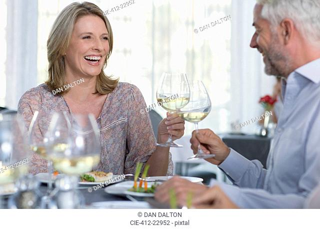 Smiling mature woman and man toasting with white wine at restaurant table