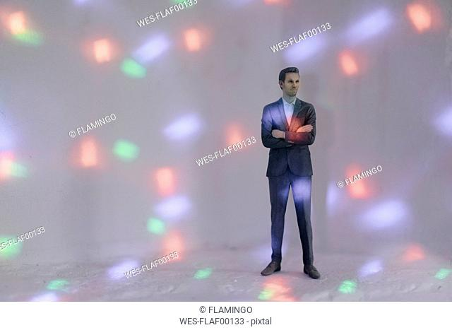 Miniature businessman figurine surrounded by points of light