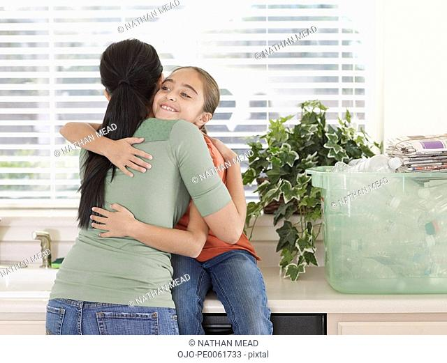 Woman and young girl in kitchen hugging near recyclable materials in a bin