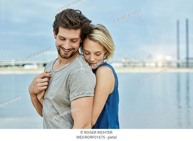 Happy young couple hugging at the riverbank