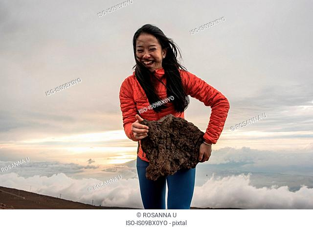 Woman carrying large rock on edge of mountain, Haleakala National Park, Maui, Hawaii