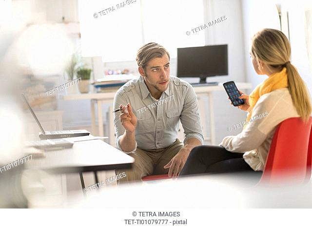 Young man and woman discussing at desk in office