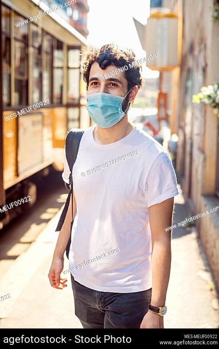 Young man wearing mask walking on city street during sunny day