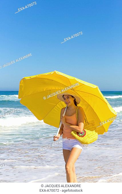 woman walks at the beach with umbrella