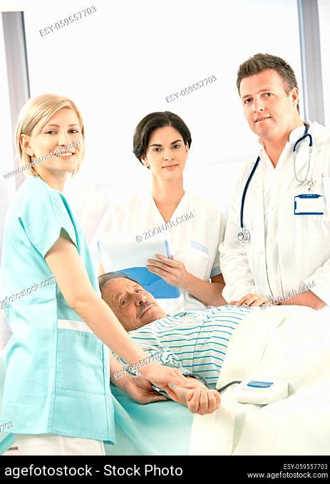 Portrait of medical team with old patient in hospital, smiling nurse measuring blood pressure
