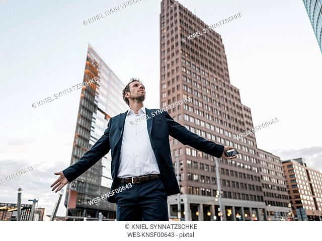 Germany, Berlin, businessman with arms outstretched standing at Potsdamer Platz in the evening