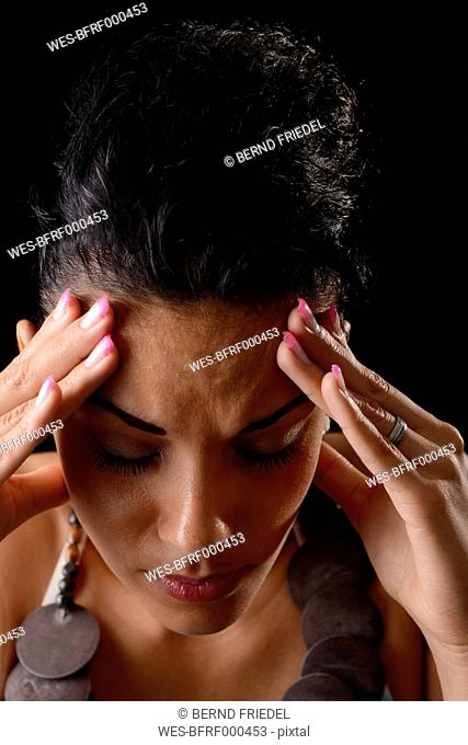Portrait of young woman with hands on her forehead in front of black background