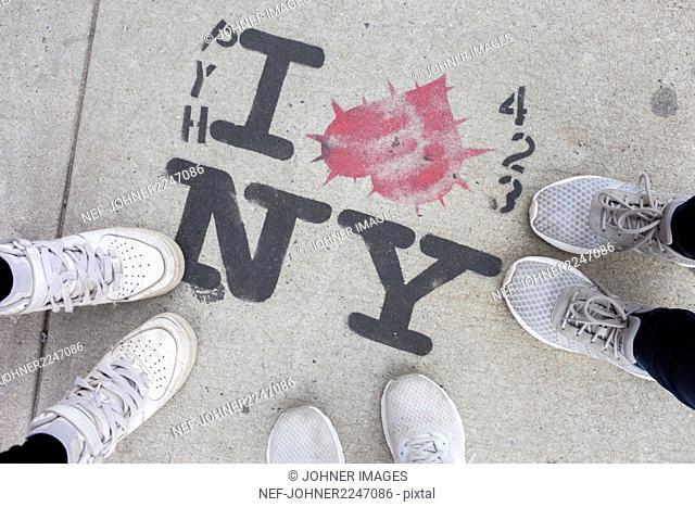 People standing around graffiti on sidewalk