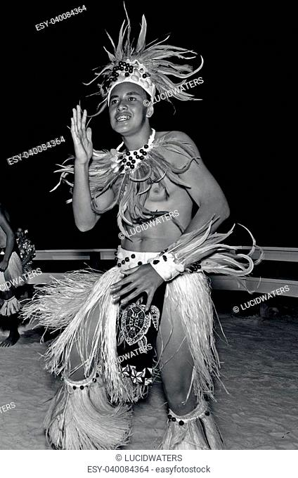 Polynesian Pacific Island Tahitian male dancer in costume dancing on tropical beach. (BW)