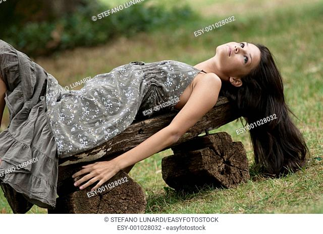 Beautiful young woman relaxing in nature, lying on a wood bench  Taken in Lipica, Slovenia  Concept: teenagers and nature