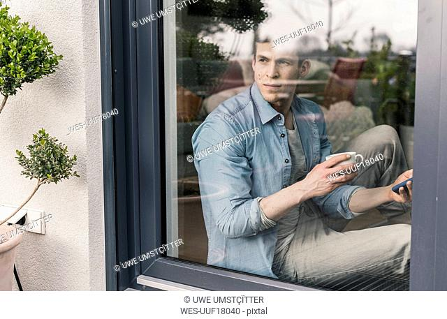 Man sitting st the window, drinking coffee