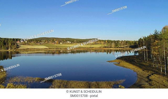 Aerial shot of a glassy lake with farm houses on a sunny autumn day. Skalmsjö, Bredbyn, Västernorrland, Sweden, Europe