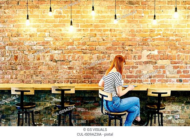 Female customer sitting at brick wall bench browsing digital tablet in coffee shop