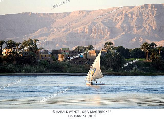 Sailing boat on the Nile River in front of a village and a rocky landscape, near Luxor, Egypt, Africa