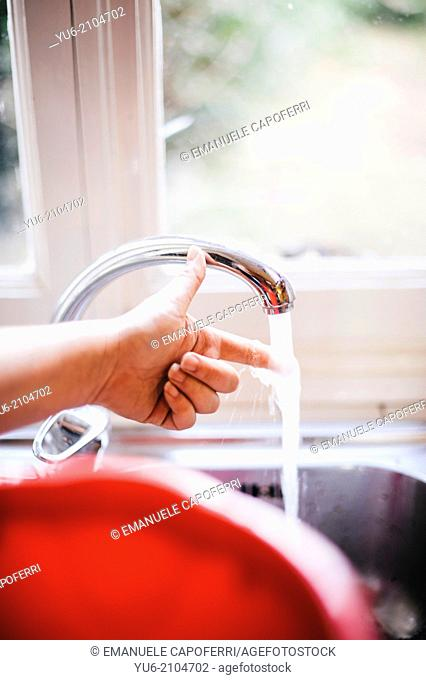 Water flows from the tap in the kitchen and a finger if it feels hot