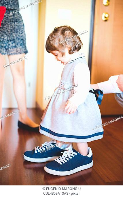 Female toddler wearing large trainer shoes