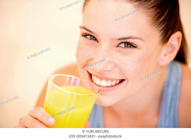 Healthy young woman holding a glass of fresh orange juice