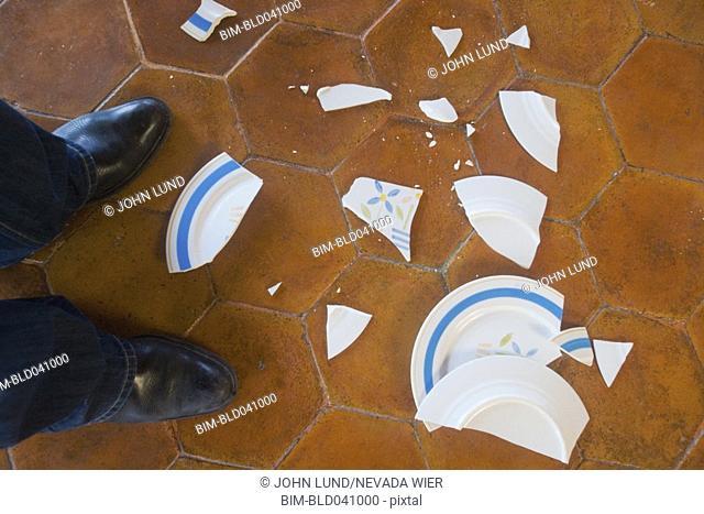 Broken plate next to man's feet