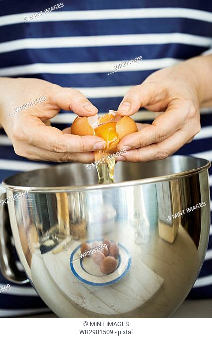 Close up of person wearing a blue and white stripy apron separating egg over a metal bowl