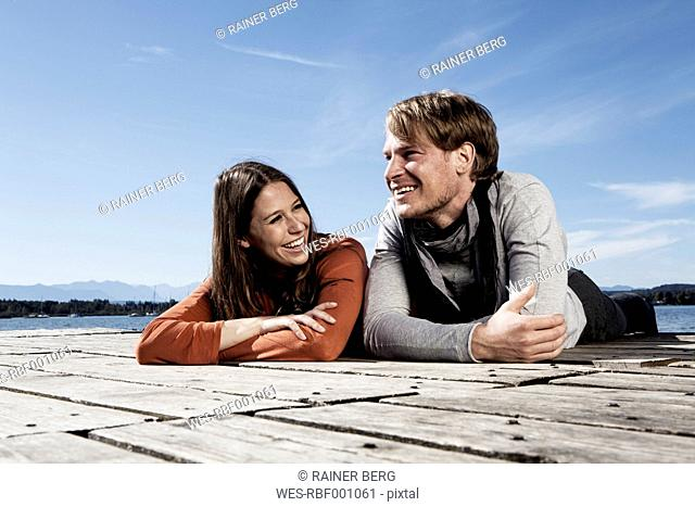 Germany, Bavaria, Couple lying on jetty at Lake Starnberg