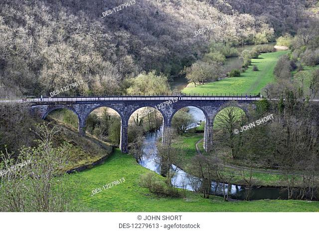 A bridge with arches crossing a small river in a valley; Derbyshire, England