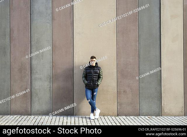 Happy young guy leaning on colored wall hands on pocket, looking camera