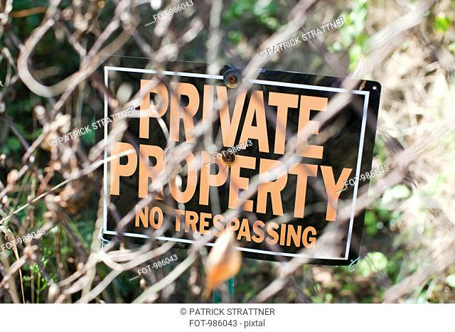 A NO TRESPASSING sign behind a chain-link fence