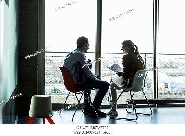 Two colleagues sitting at the window talking