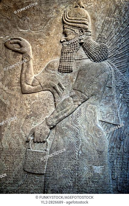Assyrian relief sculpture panel of a protective spirits, from Nimrud, Iraq. The spirit is holding a symbolic fir cone and is sprinkling holy water from the...