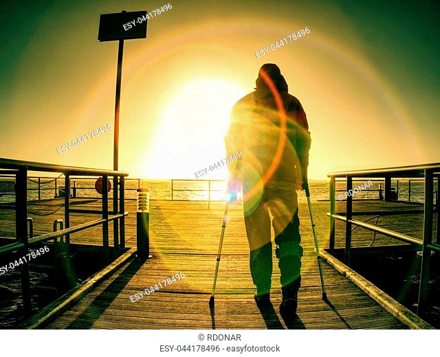 Gloomy nostalgic silhouette of sad lonely melancholic adult man with hooded jacket standing on lake bridge within early morning and thinking