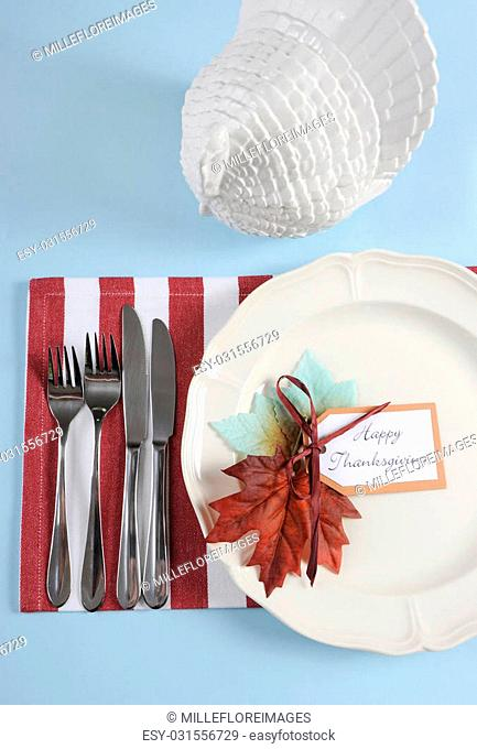 Happy Thanksgiving dining table place setting in modern pale blue, red and white theme with vintage turkey tureen. Vertical