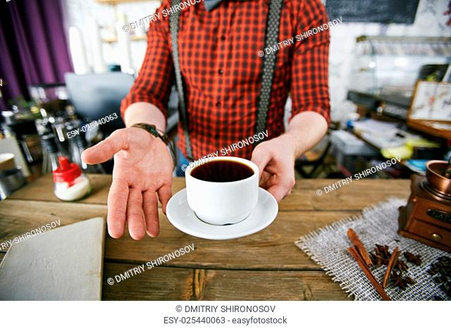 Barman holding cup of black coffee over workplace