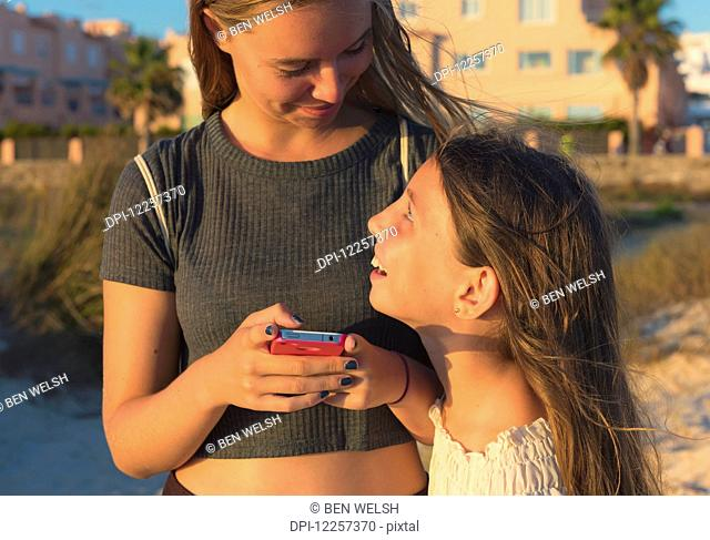 Sisters together with a cell phone; Tarifa, Cadiz, Andalusia, Spain