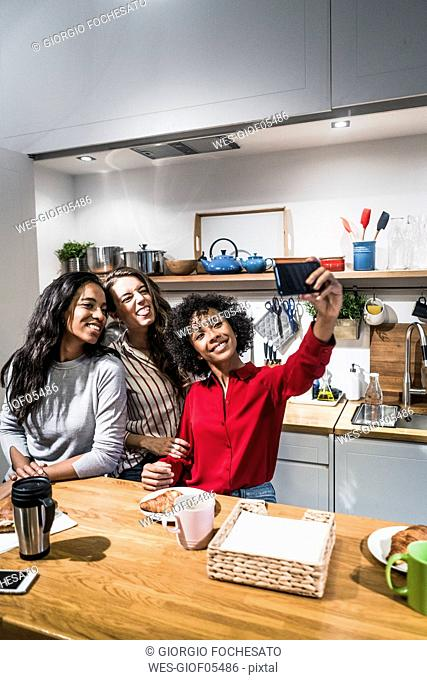 Three happy women posing for a selfie at table