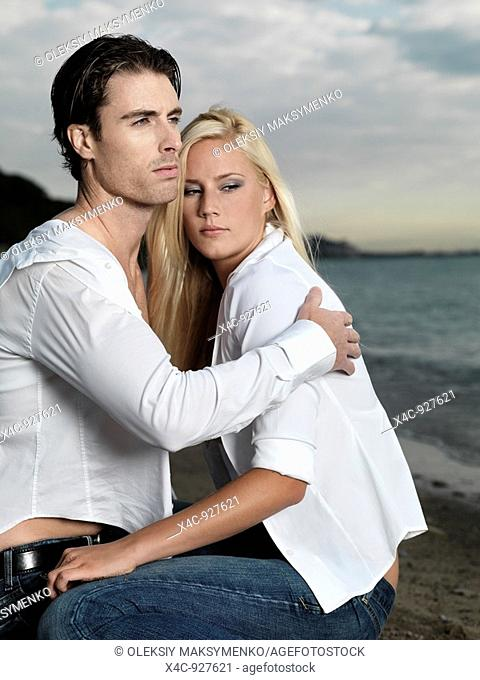 Young man and a woman sitting on the beach
