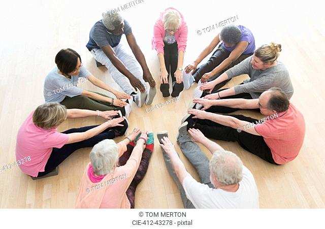 Active seniors stretching legs in circle in exercise class