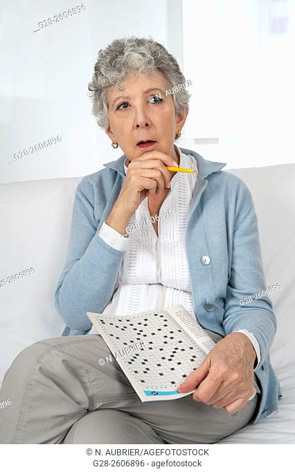 Senior woman with grey hair, busy making a crossword, thoughtful, pen in hand