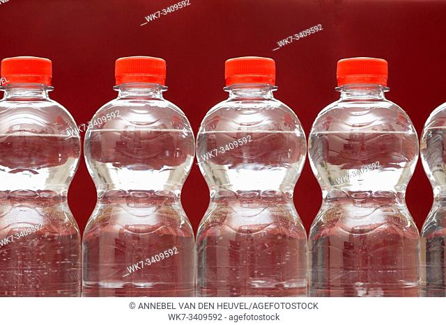 Row of water bottles, bubbling spa red, recycling environment concept close-up