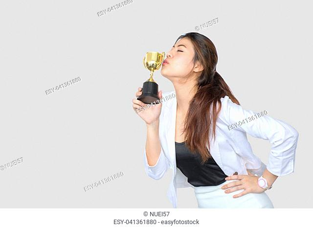 Businesswoman holding trophy award for success in business ,isolated on gray background