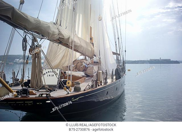 Vintage sailboat (Mariette 1915) moored in the port of Mahon, drying sails. Minorca, Balearic Islands, Spain