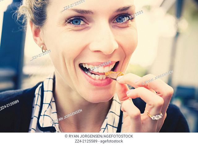 Close horizontal lifestyle picture on the face of a smiling woman eating chocolate pieces with caramel centre