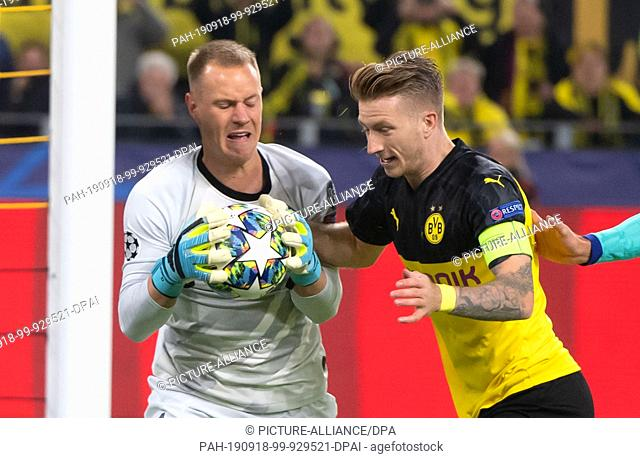 17 September 2019, North Rhine-Westphalia, Dortmund: Dortmund's Marco Reus (right) and Barcelona goalkeeper Marc-Andre ter Stegen try to get the ball after the...