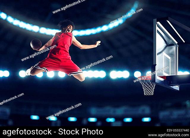 Basketball player slams dunk the ball to the basket